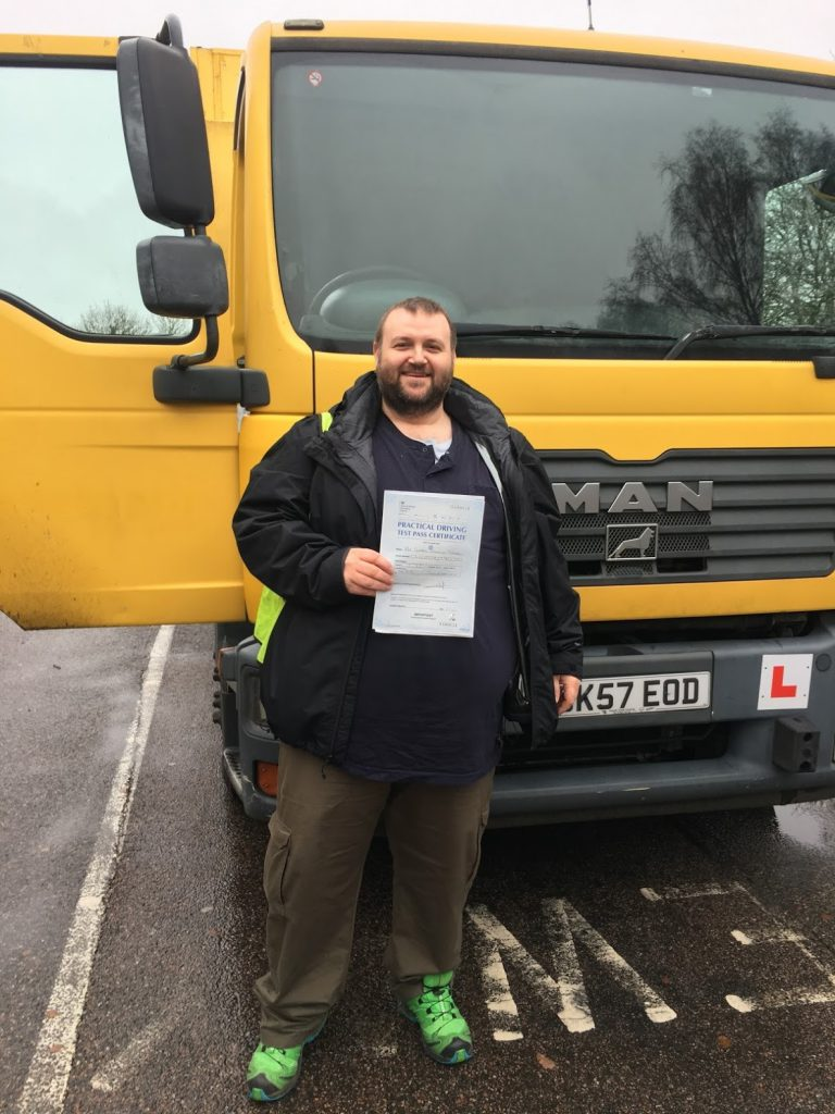 George stands in front of the lorry he took his driving test in, holding the driving test pass certificate