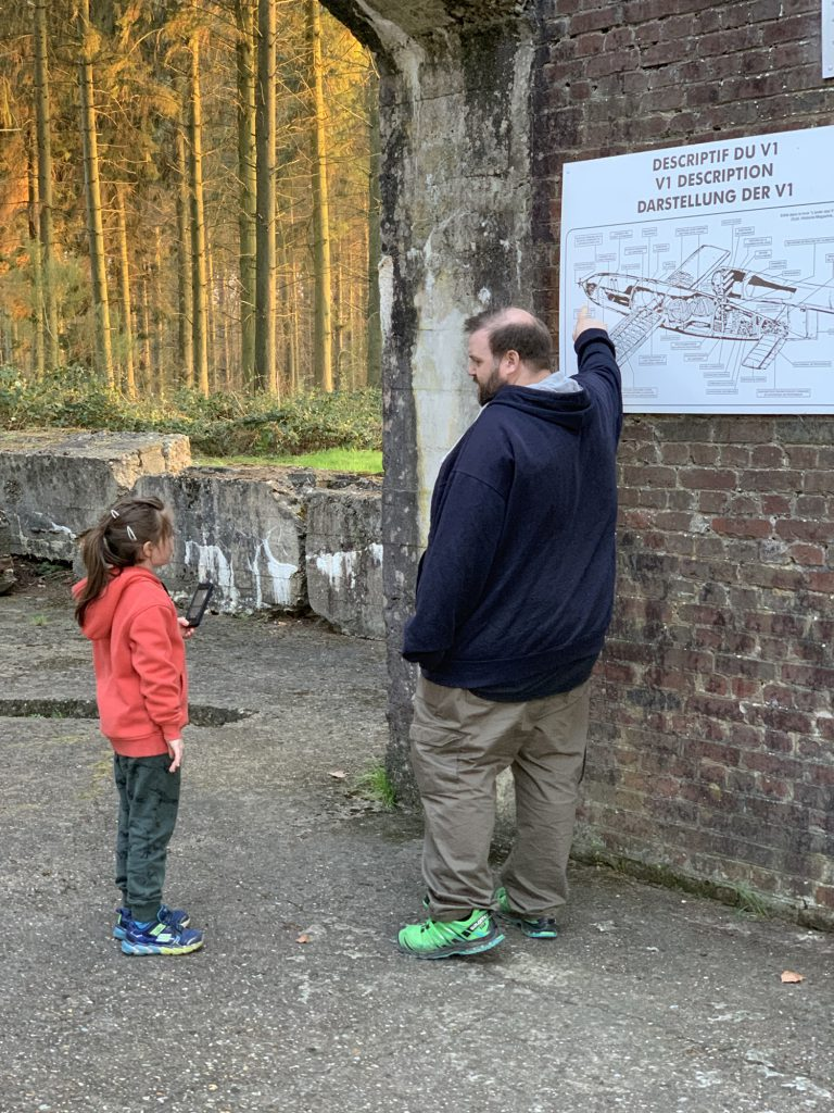 George points to a cutaway drawing of a V1 while Olivia looks on