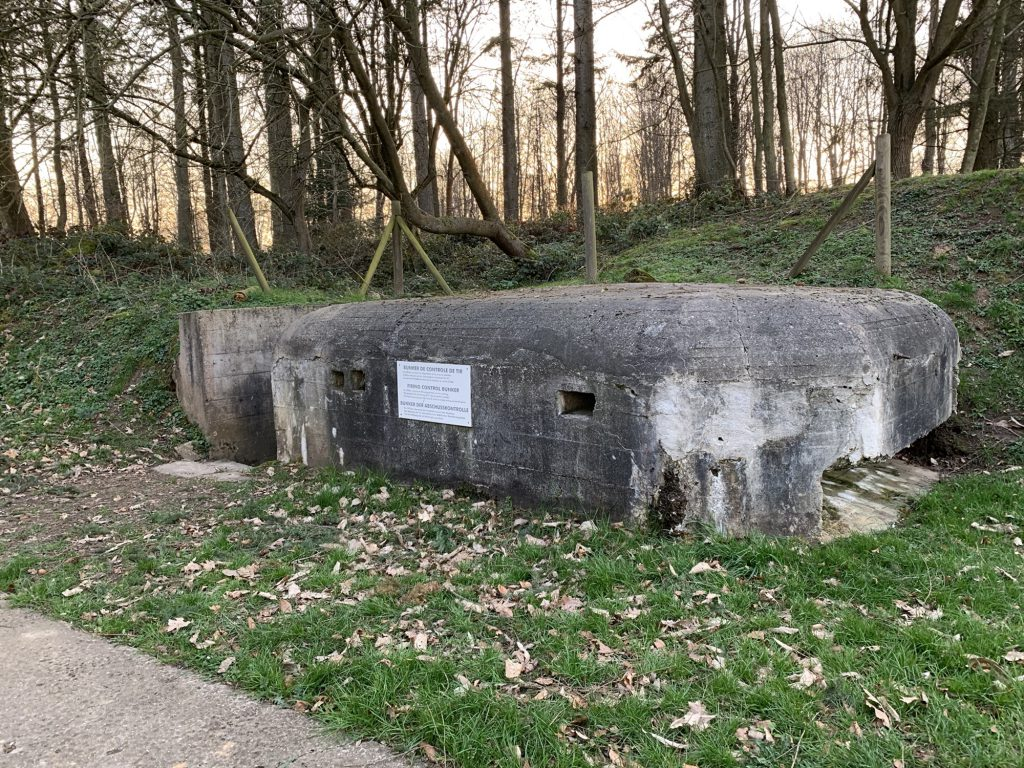 A bunker, half hidden in the ground, with a reinforced glass window in front
