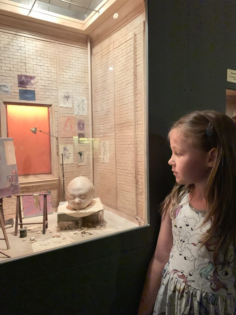 Olivia looking at miniture art studio
