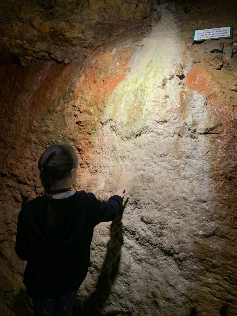 Olivia touching ochre in the cave