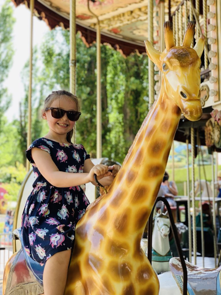 Olivia on a giraffe on the carousel at Touroparc Zoo
