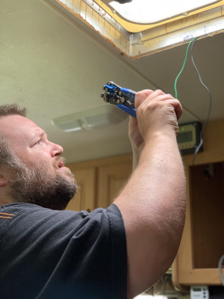 George uses a crimping tool to prepare the wiring for the MaxxFan