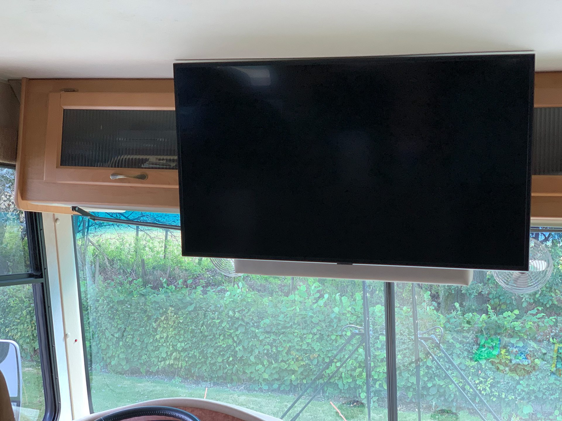 The TV is moved up close to the ceiling, showing that it doesn't hang low under the cupboards