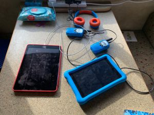 Mobile devices, iPad, Kindle Fire, Walkie Talkie and Headphones charging on a table