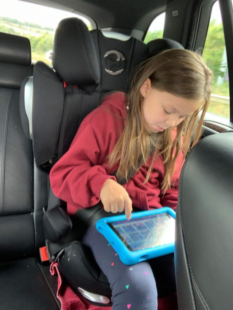Olivia sits in her travel seat, playing with her blue tablet