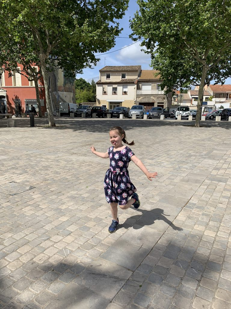Olivia runs through a village square, tongue sticking out and happy