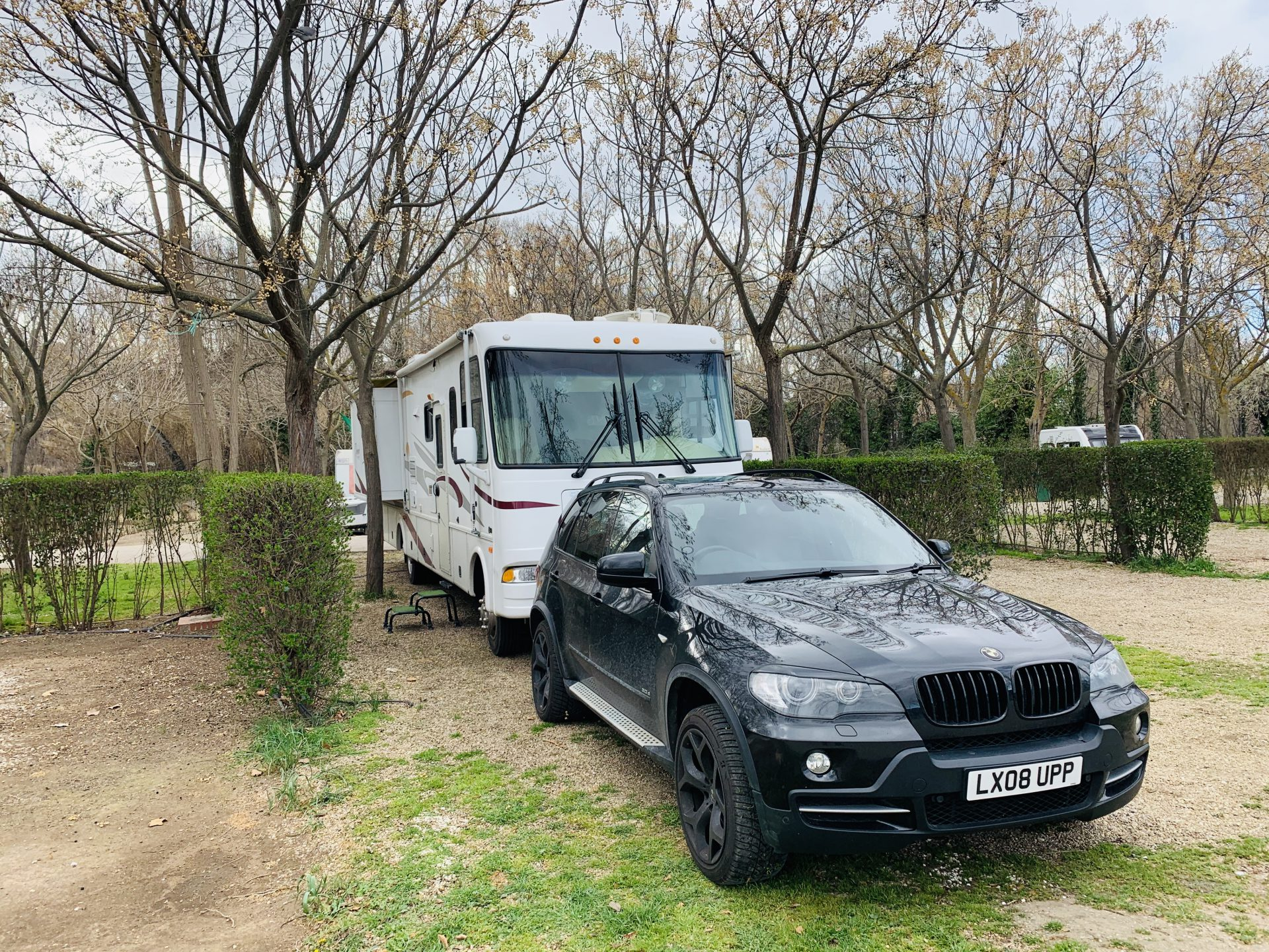 RV and BMW parked under trees